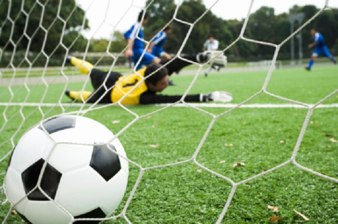 Soccer, view through net of players scoring goal, soccer ball in foreground