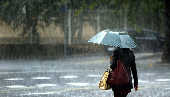 epa05007136 A woman walks under an umbrella during heavy rainfall in Valencia, eastern Spain, 02 November 2015. The authorities warned of heavy rainfall in the eastern part of country and ports in Valencia and Gandia were forced to close. EPA/KAI FOERSTERLING