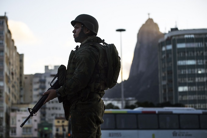 Military troops patrol Botafogo neighbourhood in Rio de Janeiro, Brazil, on July, 28, 2017. Brazil has mobilized some 8,500 soldiers to Rio de Janeiro state to fight organized crime and a spike in street violence. Some of these troops have already been deployed with transport trucks seen rolling through the city of Rio these friday afternoon. / AFP PHOTO / Mauro PIMENTEL